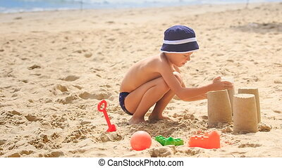 Little Boy in Hat Squats Removes Bucket to Make Sand Cake -...