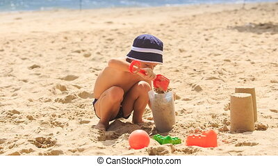 Little Boy in Hat Squats Makes Sand Cakes on Sea Beach -...