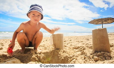 Little Boy in Hat Makes Sand Cake with Plastic Mug