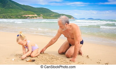 Grandpa Little Blond Girl Sit Draw on Wet Sand of Beach by Surf