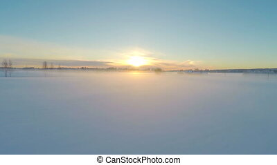 Flying over foggy snow fields in the sunset - Camera flying...