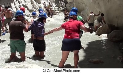 Group of tourists passing mountain torrent - Group of...