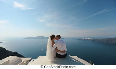 Brunette bride and groom sitting on the terrace and kissing with sea background