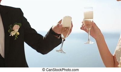 Groom and bride are drinking champagne at wedding aisle tent...
