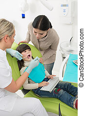 Little girl with her mother at dentist's office - Little...