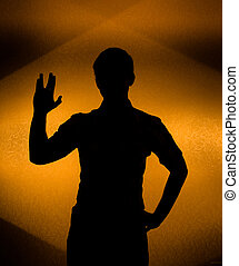 Back lit silhouette of man with raised hand - Live long -...