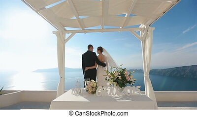 Groom and bride hugging and kissing at wedding aisle tent...