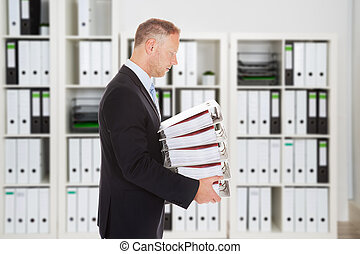 Mid Adult Businessman Carrying Binders In Office - Side view...