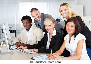 Group Of Businesspeople Looking At Computer