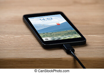 Closeup Of Smart Phone Connected To Charger - Closeup of...