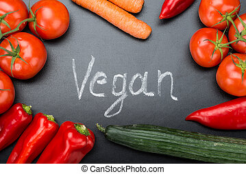 Vegan Written Amidst Fresh Vegetables On Blackboard -...