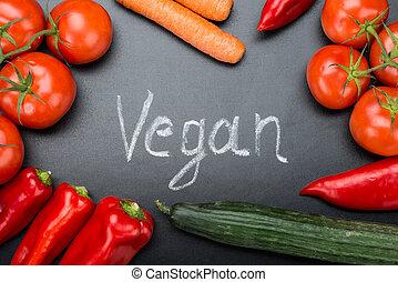 Vegan Written Amidst Fresh Vegetables On Blackboard -...
