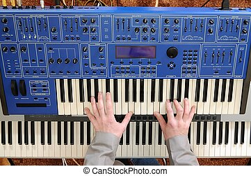 Man playing synthesizer - Mans hands playing the keyboard of...