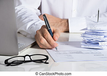 Businessman Analyzing Invoice At Office Desk