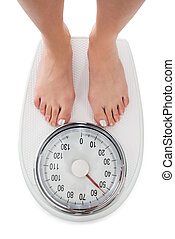 Directly Above Shot Of Woman Standing On Weight Scale -...
