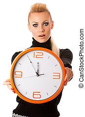 Worried woman with big orange clock gesturing delay, rush,...