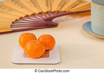 Three mandarines with a tea and a chinese fan