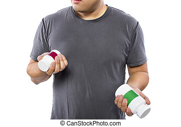 Man Comparing Brands of Dietary Supplements - Male comparing...