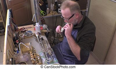 repairer of brass and wood wind - craftsman testing the key...