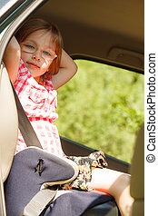 Road and safety. Little girl sitting in car seat.