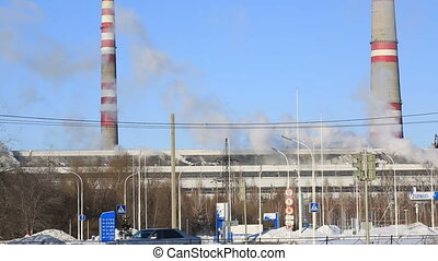 Thermal power plant in sunny cold day. Industrial smoke from the pipes against blue sky.
