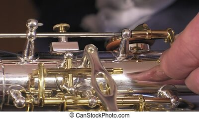 repairer of brass and wood wind - placing key rod of alto...