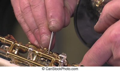 repairer of brass and wood wind - Placing saxophone alto key...