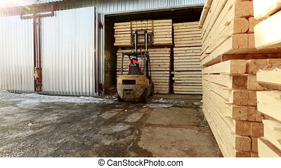 Truck loads stack of materials at warehouse in winter time