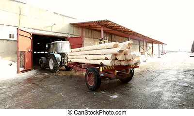 View of truck unloads logs from tractor - Sawmill. View of...