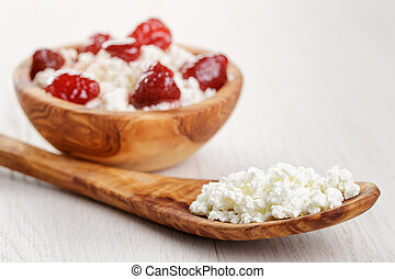 cottage cheese with preserved strawberry in wood bowl on oak...