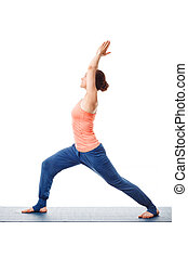 Woman practices yoga asana utthita Virabhadras - Beautiful...