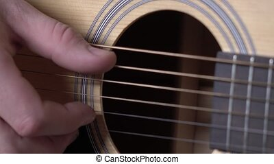 Hand of man playing guitar, close up