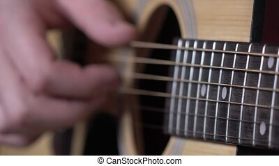 Hand of man playing guitar, focus on strings, close up -...