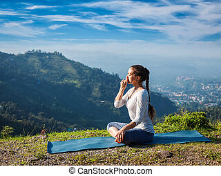 Woman practices pranayama in lotus pose outdoors - Woman...