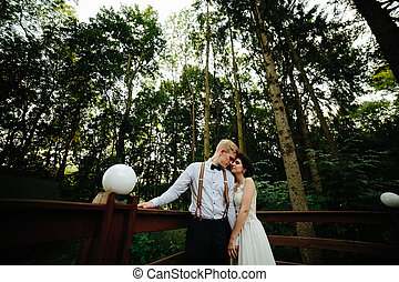 bride and groom posing on the verandah somewhere in the...