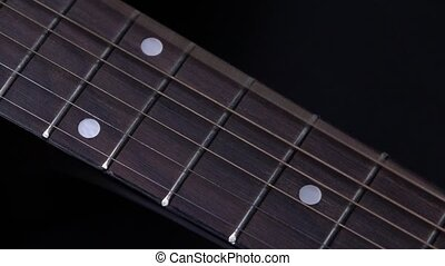 Strings of acoustic guitar, on black, close up, slow motion...