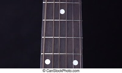 String of acoustic guitar, stands up, on black, close up,...