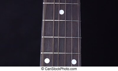 Playing string of acoustic guitar, stands up, on black,...