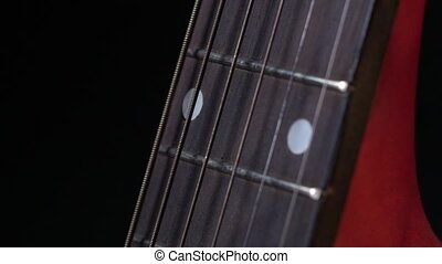 Play strings of acoustic guitar, side view, on black, close up, slow motion