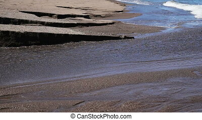 Black sand volcanic beach with creek - River flows on black...