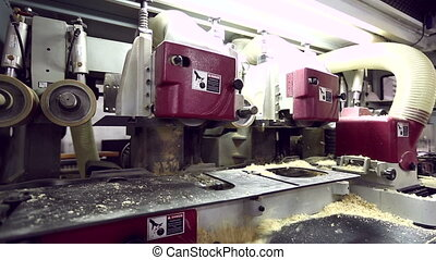 View on worker blowing sawdust from machine - Woodworking....