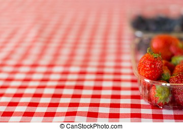 Red strawberries on a table cloth - Red strawberries on red...