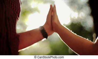 Holding hands of in love couple in green summer forest Sun...