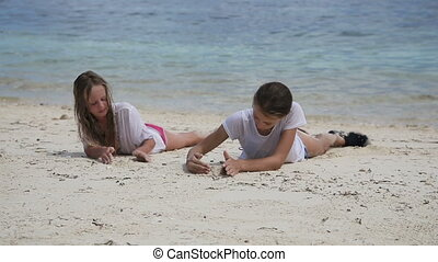 Happy girls playing with sand on beach in summer. - Young...