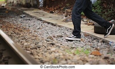Man's feet cross railway in the wrong place. Summer day. -...