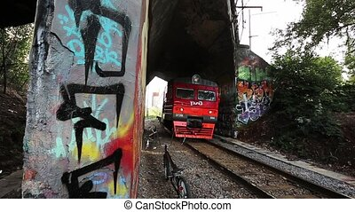 Moving suburban electric train under bridge moves on camera. Graffiti