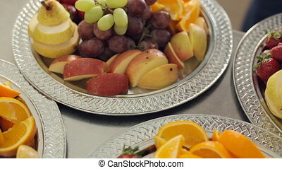 Fresh delicious pear, orange, apple, strawberries and grapes lying on a large silver platter with a mint