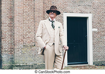 Smiling well dressed senior man standing with cane in front of building.
