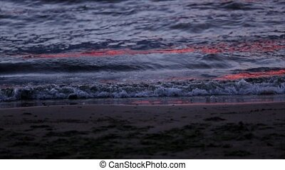 Sea waves gently wash up after red sunset. Slow motion. Nobody