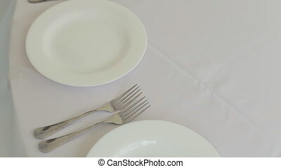 The waiter served table with eating utensils on a banquet -...